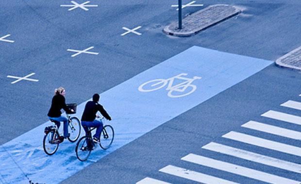 Pareja en bicicleta atravesando una calle señalizada